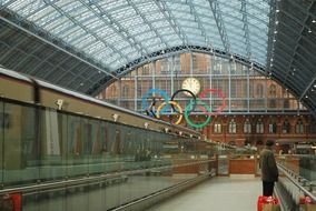 a train station in London against the backdrop of the Olympic Games symbol