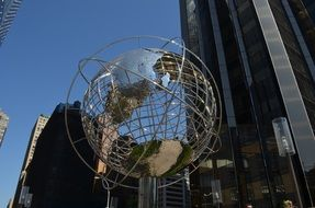 globe-shaped monument against the background of a skyscraper