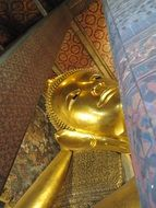 golden buddha statue between buildings