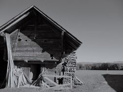 black and white photo of an old barn on a field