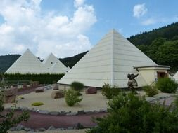 white pyramids near a green hill