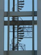 spiral staircase behind window of modern building