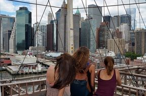 Girls watching from the bridge to the skyscrapers of new york