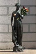 bronze statue of a woman with flowers