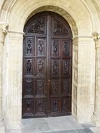 arched portal of cathedral with carved wooden door, spain, salamanca