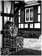 black and white photo of firewood near a house in Gengenbach