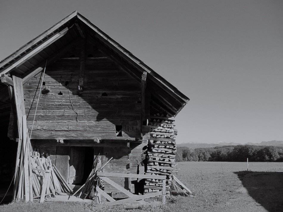 black white photo of an old barn on a field