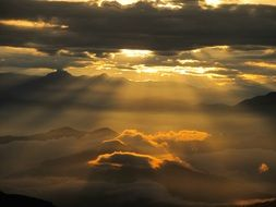 the golden rays of the sun illuminate the dark clouds