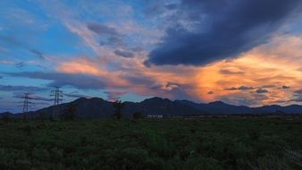 panorama of mountains and high-voltage towers at sunset