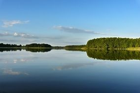 summer panorama of a wide lake and green forest