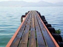 perspective of wooden pier on calm water in view of mountains, south africa