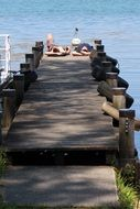 two young men lay on boardwalk at water
