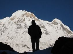 silhouette of a wanderer on the background of the snow mountain of Annapurna in the Himalayas