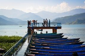 row of boats at pier on lake fewa in scenic landscape, nepal, pokhara