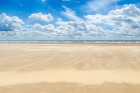 clear sky with white clouds over a sandy beach