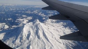 view of snow mountain from an airplane window