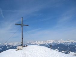 cross at the peak of a snowy mountain in Wagrain, Austria