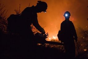 fire fighters with chain saw at night