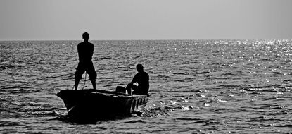 black and white photo of fishermen in a boat