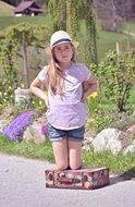 child girl blond hat with personal luggage