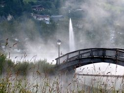 bridge in the haze on the background of the fountain