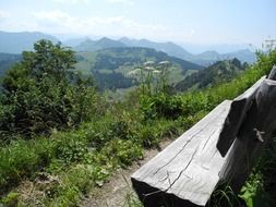 wooden bench in front of scenic mountains at summer