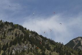 parachutists in the sky near mountains