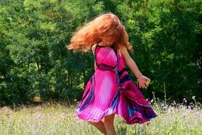 red-haired girl in a purple dress is dancing in a meadow