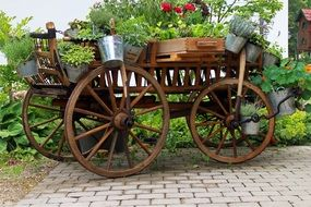 decorative wooden wagon with shiny buckets in a garden