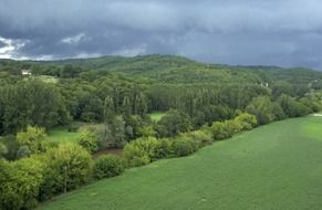 panoramic view of storm clouds over a green forest