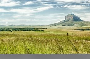 green grassland and scenic rock at cloudy sky, south africa