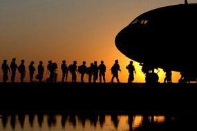 the soldiers at the plane against the backdrop of an orange sunset