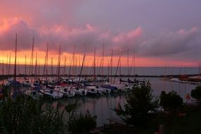 sailboats on a pier on Lake Balaton on a background of purple sunset