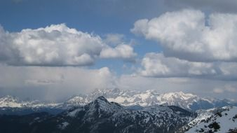 white clouds over the alpine mountains