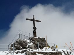 cross on top of a snowy mountain