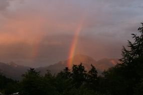 rainbow in the evening sky over the mountains