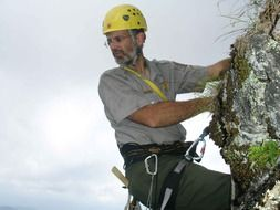 mountaineer in a yellow helmet close-up