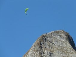 glider soars over a mountain ridge