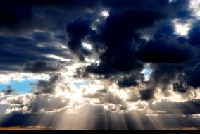 bright sunbeams through dark blue clouds in the evening sky