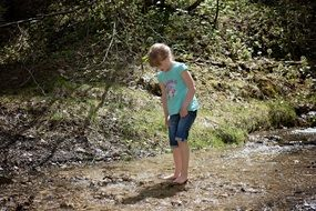 girl stands barefoot in a forest stream