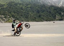 motorbiker jumping on sand at mountains, indonesia, east java