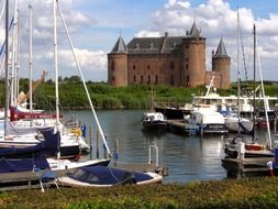 boats on lake in view of medieval castle Muiderslot, netherlands, muiden