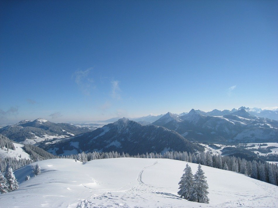 view of the snowy mountain landscape on the background of the sunny sky