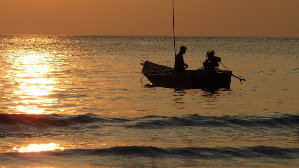 Fishermen on a boat at sunset