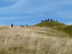 people near the cross on a hill in the alps