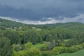 picturesque green valley on the background of the cloudy stormy sky