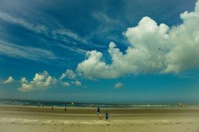 scenic row of white fluffy clouds in sky above beach