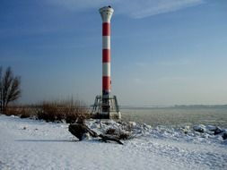 high lighthouse tower on river bank in winter