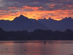 purple and orange clouds above mountains and lake, switzerland, lucerne