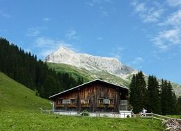 wooden cottage on the background of the Arlberg mountain range